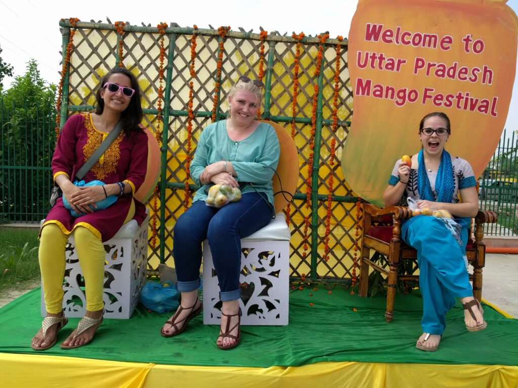 Three women sitting in front of UP Mango festival sign